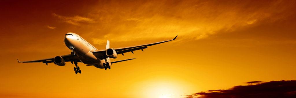 avião no ar e sol se pondo ao fundo