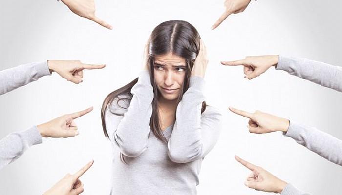 Mulher com medo e vários dedos apontando para ela